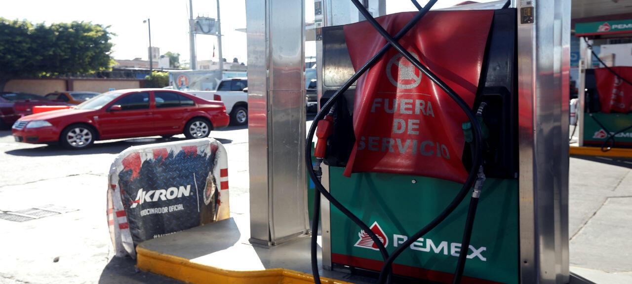 """Un surtidor de combustible con una pancarta que dice """"Fuera de servicio"""" se aprecia en una gasolinera de la empresa estatal Petróleos Mexicanos (Pemex), que está cerrada por falta de combustible, en Guadalajara, México, el 6 de enero de 2019."""