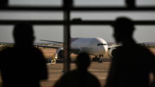 Des touristes regardent en direction d'un avion russe, à l'aéroport de Charm el-Cheikh, le 6 novembre 2015.