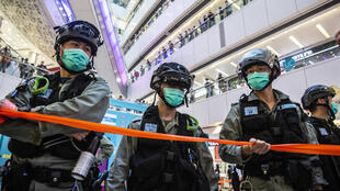 Riot police stand guard during a clearance operation in a mall in Hong Kong on July 6, 2020, in response to a new national security law that makes political views, slogans and signs advocating Hong Kong's independence or liberation illegal.