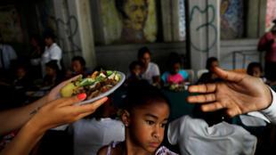 Una niña observa a los voluntarios del candidato presidencial venezolano Javier Bertucci entregando platos de comida a mujeres y niños como parte de la celebración del Día de las Madres, durante un mitin de campaña en Caracas, Venezuela, el 13 de mayo de 2018.