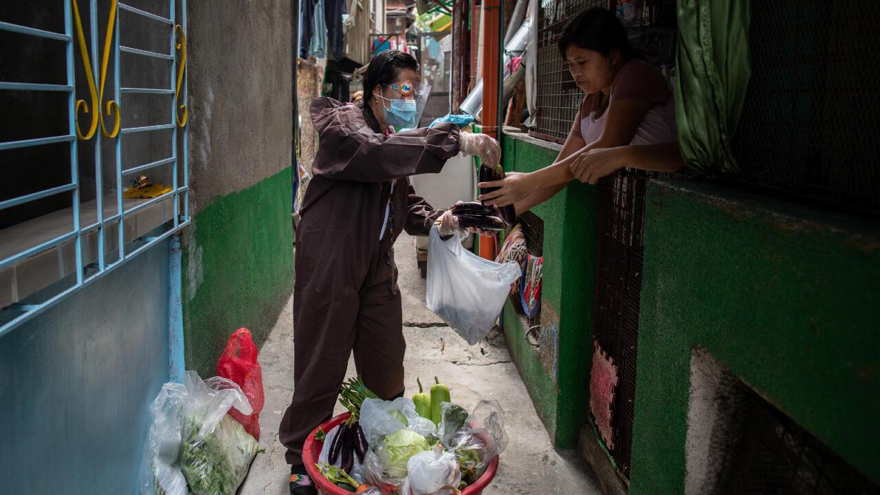Un trabajador del gobierno con traje de protección vende alimentos en Navotas, Metro Manila, Filipinas, en medio de una nueva medida de confinamiento en la capital y sus alrededores este 6 de agosto de 2020.