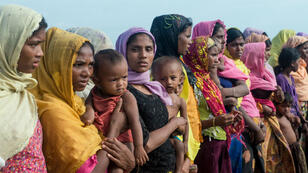In this photograph taken on November 12, 2017, women hold children at a makeshift camp in Rakhine state in Myanmar, where hundreds of Rohingya Muslims wait in makeshift camps before finding a way to cross over into Bangladesh. Torched villages and unharvested paddy fields stretch to the horizon in Myanmar's violence-gutted Rakhine state, where a dwindling number of Muslim Rohingya remain trapped in limbo after a violent military crackdown coursed through the region.