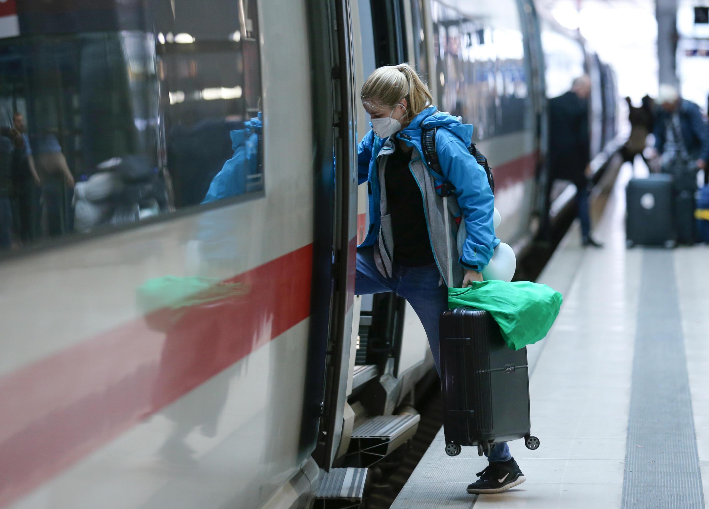 امرأة ترتدي الكمامة الواقية أثناء صعودها في القطار - ألمانيا