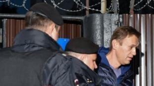 عنصران من الشرطة الروسية يعتقلان المعارض ألكسي نافالني أمام سجن في موسكو في 24 أيلول/سبتبمر 2018