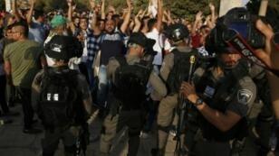 فلسطينيون يهتفون أمام قوات الأمن الإسرائيلية في الحرم الشريف في القدس في 27 تموز/يوليو