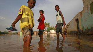 صبية سودانيون في شارع غمرته المياه في أم درمان بتاريخ 26 آب/اغسطس 2020