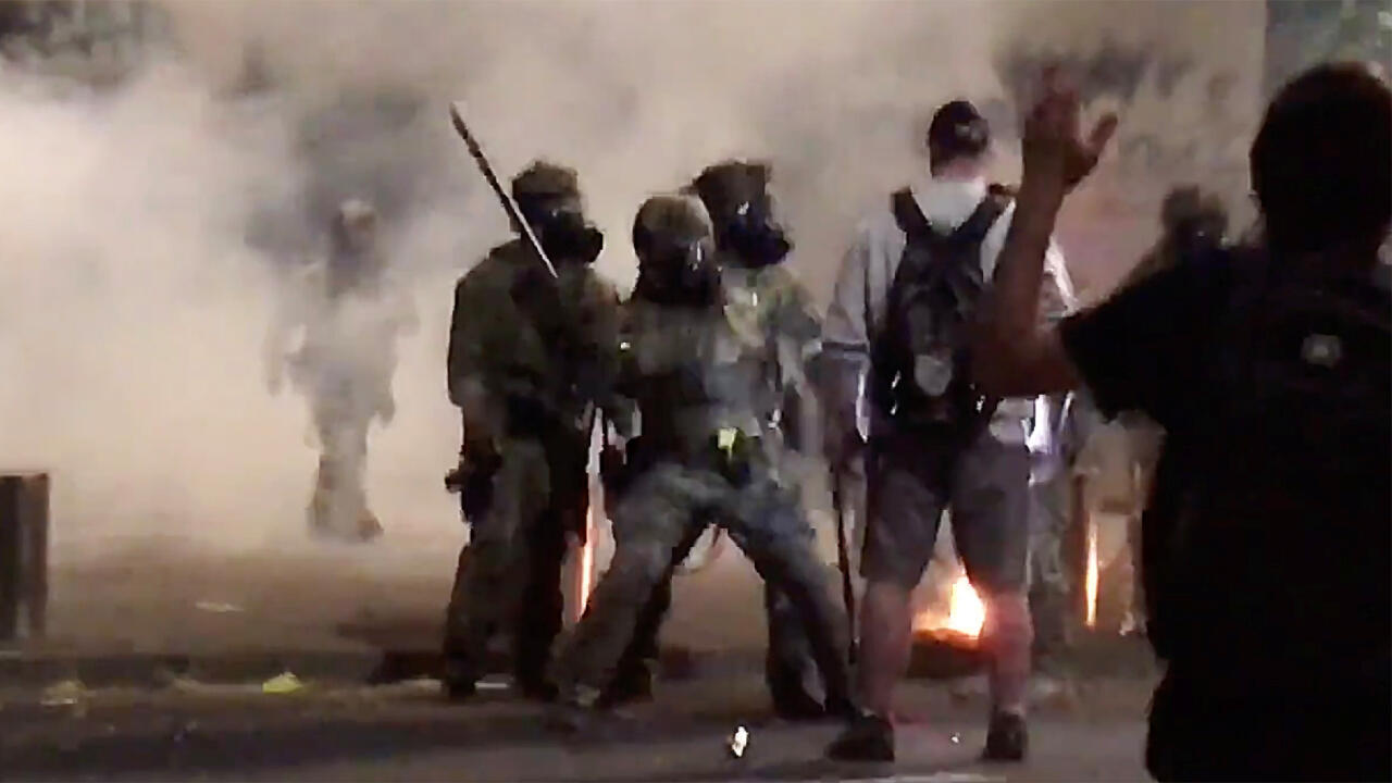 A man is struck by a police officer during a protest against racial inequality in Portland, U.S., July 18, 2020, in this still image obtained from a social media video.