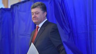 Ukrainian President Petro Poroshenko holds his ballot in a polling station in Kiev on October 26, 2014, during Ukraine's parliamentary elections.