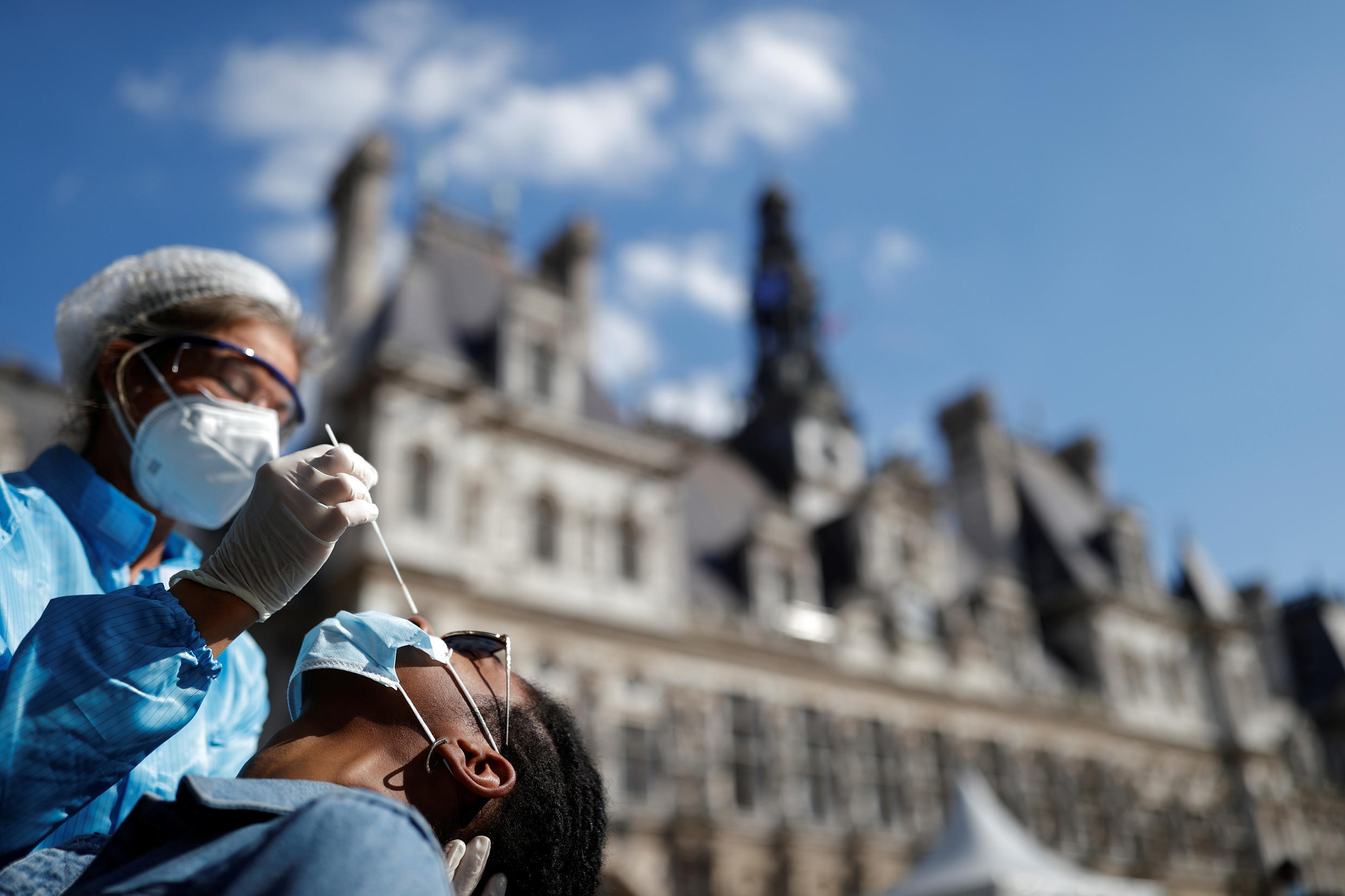 A health worker, wearing a protective suit and a face mask, prepares to administer a nasal swab to a patient at a testing site for Covid-19 installed in front of the city hall in Paris, France, September 2, 2020.