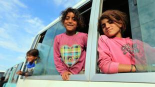 Familias desplazadas, que huyeron de la violencia después de la ofensiva turca en Siria, en un autobús camino a un campo de refugiados en Bardarash, en las afueras de Dohuk, Irak, el 25 de octubre de 2019.