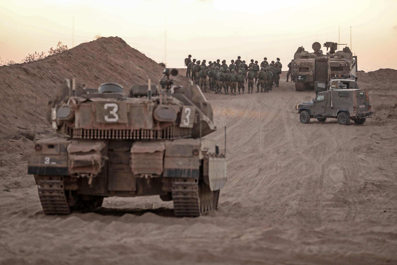 عناصر من الجيش الإسرائيلي أمام دبابات وحاملات جنود.