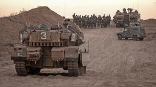 عناصر من الجيش الإسرائيلي أمام دبابات وحاملات جنود قرب الحدود بين إسرائيل وقطاع غزة بتاريخ 16 آب/اغسطس 2020
