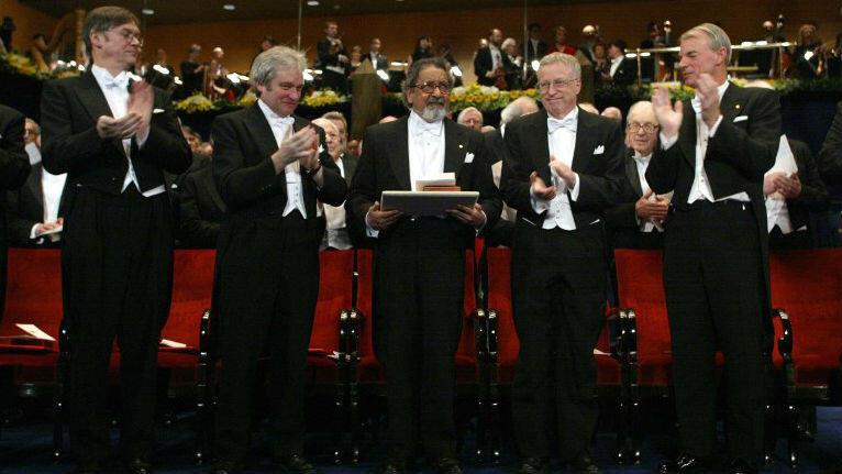 V.S. Naipaul, ganador del Premio Nobel de Literatura 2001, aplaudido por otros galardonados en Estocolmo.
