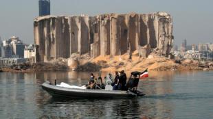 Des membres de l'armée libanaise et de l'armée française passent en zodiac devant le silo à grains éventré par l'explosion du port de Beyrouth, le 31 août 2020