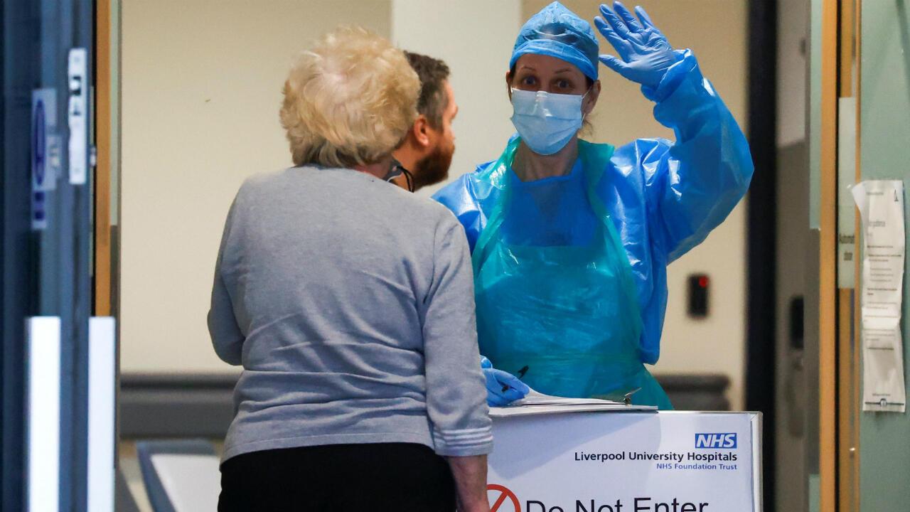 """Una trabajadora del NHS saluda junto a un cartel que dice """"no entrar"""" en el Hospital de la Universidad de Aintree durante una manifestación de apoyo al servicio sanitario. Liverpool, Reino Unido, el 23 de abril de 2020."""