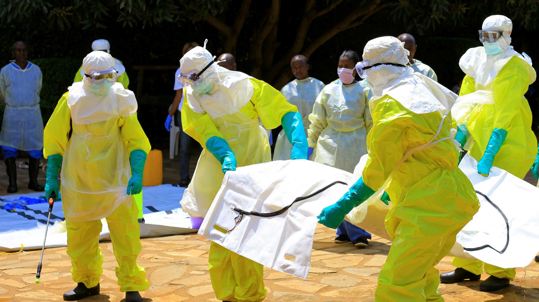 Funcionarios congoleños y de la Organización Mundial de la Salud usan trajes de protección cuando participan en un entrenamiento contra el virus del Ébola cerca de la ciudad de Beni en la provincia de Kivu, norte de la República Democrática del Congo, el 11 de agosto de 2018.