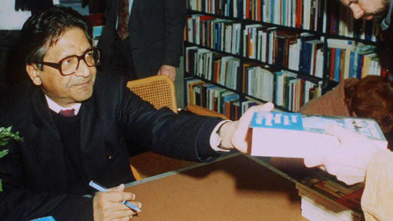 """El escritor de Trinidad y Tobado Vidiadhar Surajparasad Naipaul firma el 13 de enero de 1991 en Ámsterdam la traducción holandesa de su novela reciente """"India: A Million Mutinies Now""""."""
