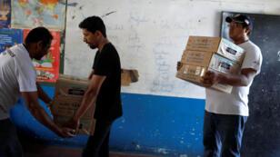 Voluntarios llevan papeletas a un centro de votación dentro de una escuela antes de las presidenciales en Cuscatancingo, El Salvador, el 1 de febrero de 2019.
