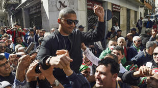 "Algerian protesters carry journalist Khaled Drareni on their shoulders on March 6, 2020, the day before he was arrested while covering an anti-government protest, accused of ""inciting an unarmed gathering"""