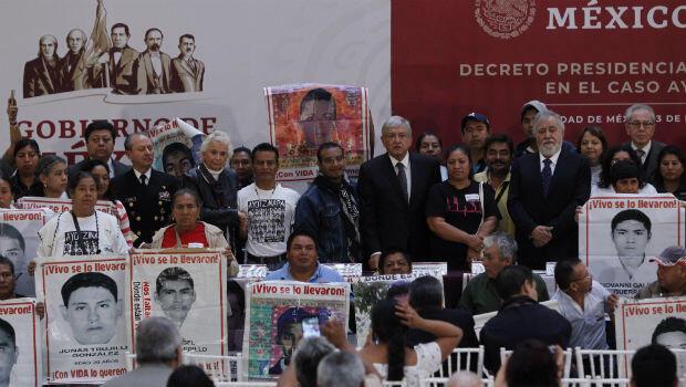 El presidente de México Andrés Manuel López Obrador posa con familiares de los 43 normalistas desaparecidos en Ayotzinapa, durante la firma del decreto presidencial para la instalación de una Comisión de la Verdad el 3 de diciembre de 2018 en Ciudad de México.