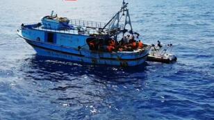 Des garde-côtes italiens, lors d'une opération de sauvetage d'un bateau de migrants, le 30 août 2016.