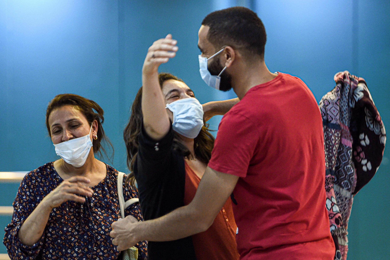 Une femme tunisienne masquée arrivant de France et embrassant les membres de sa famille à l'aéroport international de Tunis, le 27 juin 2020.