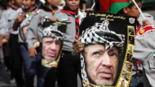 Des enfants portent des portraits de Yasser Arafat à l'occasion d'une marche pour le 9e anniversaire de sa mort en novembre 2013.