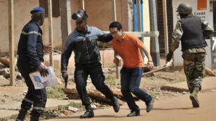 Les forces desécurité maliennes évacuant un client de l'hôtel Radisson Blu de Bamako, théâtre d'une prise d'otages vendredi.