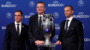 El excapitán de Alemania y embajador de la candidatura, Philipp Lamm (izquierda), el presidente de la Federación Alemana de Fútbol, Reinhard Grindel (centro), y el presidente de la UEFA, Aleksander Ceferin (derecha) posan junto al trofeo de la Eurocopa tras la elección de Alemania como sede de la edición 2024 en Nyon, Suiza, el 27 de septiembre de 2018.