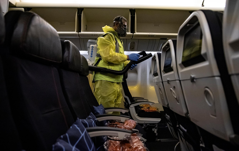 Un miembro del personal del aeropuerto Charles de Gaulle nebuliza el interior de un avión de Air France como parte de un proceso de desinfección preventiva contra el coronavirus, en la Terminal 2 del aeropuerto internacional Charles de Gaulle en Roissy, cerca de París, el 14 de mayo de 2020.