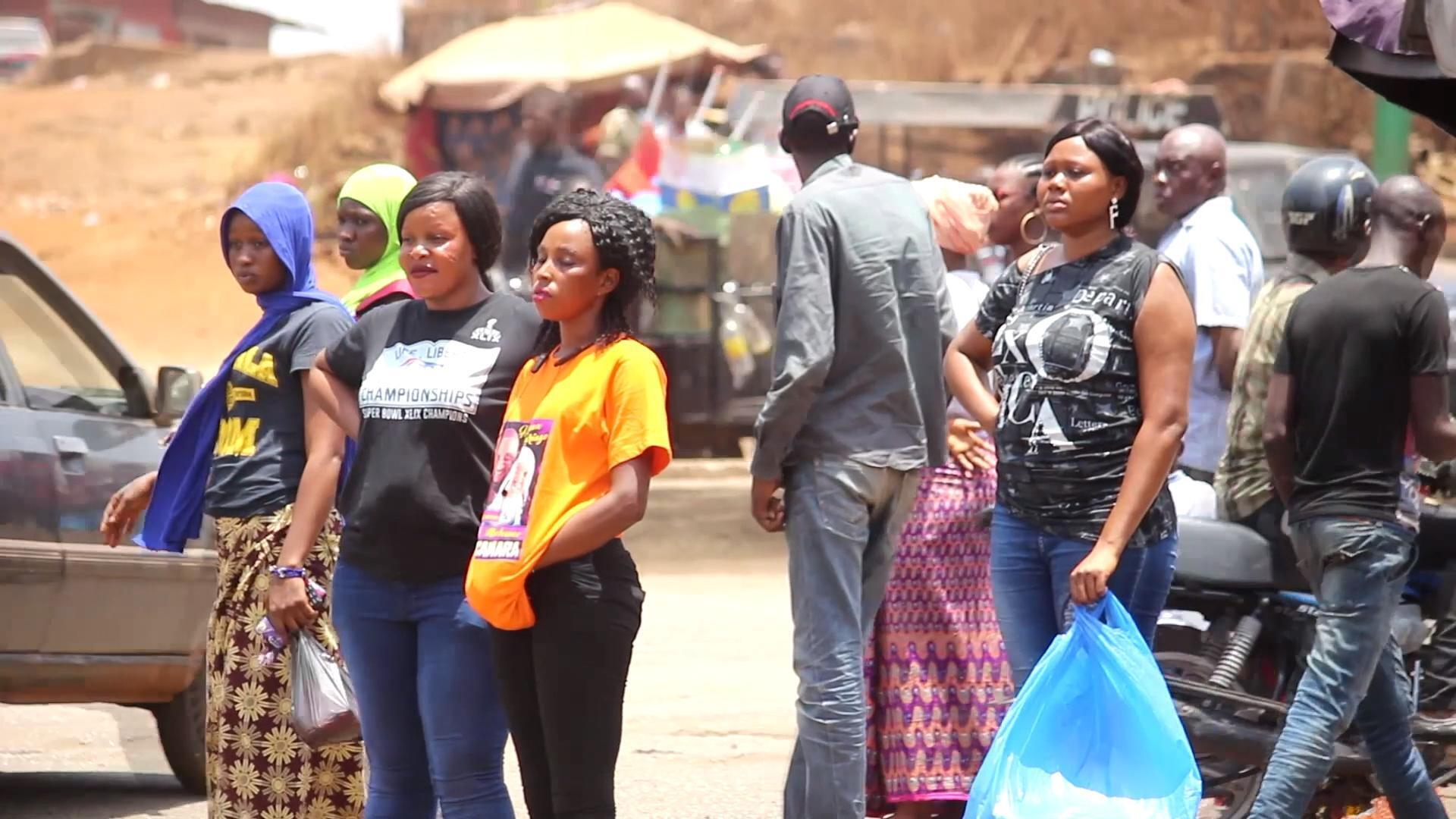 Des passagers attendent un taxi à Conakry.