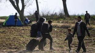 Migrants carry their belongings as they walk towards the Pazarkule border gate in Edirne on March 4, 2020, during their journey to try to enter Europe.