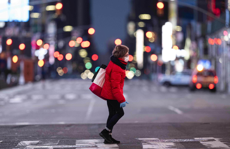 Une femme équipée d'un masque traverse un Times Square quasi désert le 23 avril 2020, à New York.
