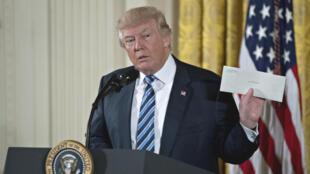 Donald Trump montre la lettre que Barack Obama lui a laissé dans le bureau ovale.