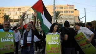 عرب إسرائيليون يحملون شعارات خلال تظاهرة ضد قانون الدولة القومية في تل أبيب في 11 آب/أغسطس 2018.