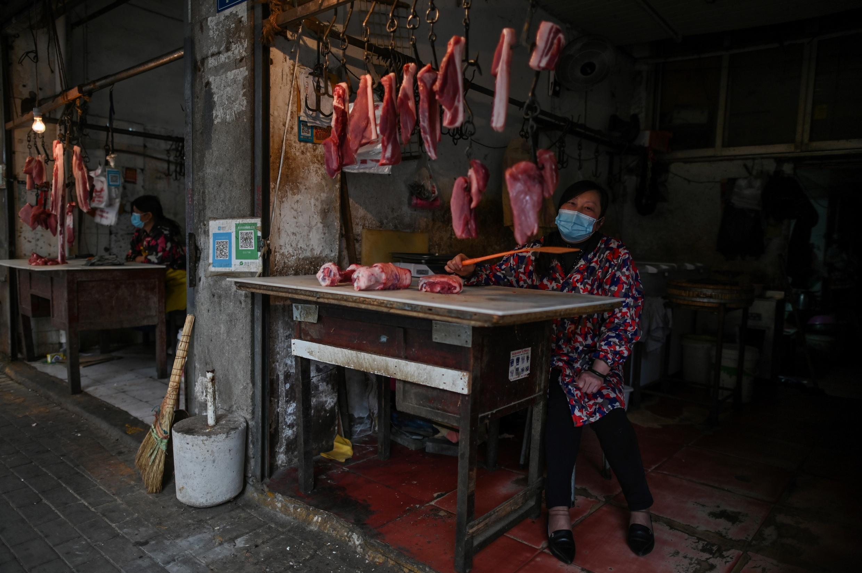 سيدة تبيع اللحم في أحد أسواق ووهان الشعبية وسط الصين حيث ظهر فيروس كورونا لأول مرة