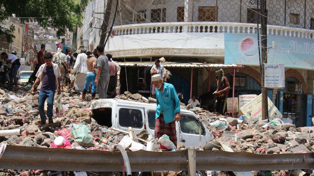 La gente inspecciona los daños causados por las inundaciones en una calle de Adén, en Yemen, el 22 de abril de 2020.
