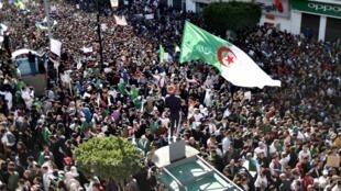 متظاهرون جزائريون يرفعون الأعلام الوطنية أمام مبنى البريد المركزي في العاصمة