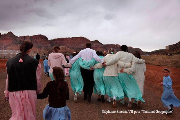 """Entouré de ses femmes, un homme assiste aux obsèques de Foneta Jossep. Il s'est marié avec plusieurs filles de Foneta, qui sont donc à la fois sœurs et co-épouses. Elles ont cousu une robe pour l'occasion, """"pour symboliser l'amour qui les unit"""", explique le mari."""