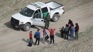 طالبو لجوء يتحدثون مع دورية أمريكية بعد عبور الحدود مع المكسيك في 7 تشرين الثاني/نوفمبر 2018 في ميشن في ولاية تكساس