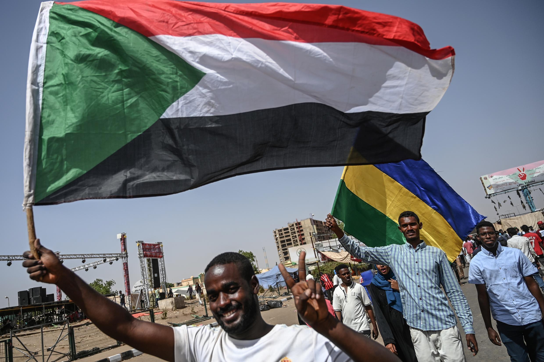 متظاهرون سودانيون يلوحون بعلمي بلادهم الرسمي والتقليدي في الخرطوم في 27 أبريل نيسان 2019