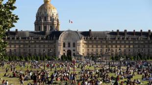 Des personnes prennent le soleil dans les jardins de l'Esplanade des Invalides, le 28 mai 2020 à Paris