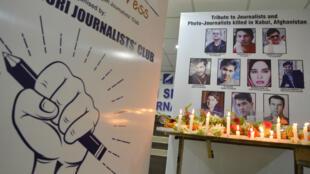 Velas rodean las imágenes de periodistas afganos que murieron en un atentado suicida durante una vigilia para conmemorar el Día Mundial de la Libertad de Prensa en la ciudad india de Siliguri, el 3 de mayo de 2018.