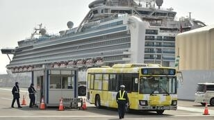 A bus carrying passengers from the Diamond Princess cruise ship (back) leaves the Daikoku Pier Cruise Terminal in Yokohama, Japan, on February 20, 2020.