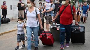 Canadienses fuera del consulado de su país en Lima, antes de abordar autobuses que los llevarán al aeropuerto Jorge Chávez para ser repatriados, tras el cierre de fronteras ordenado por Perú debido a la pandemia de coronavirus, el 26 de marzo de 2020