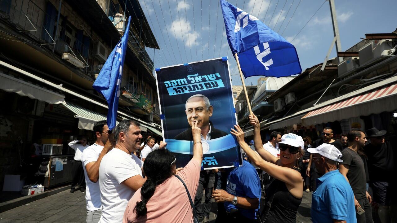 Una serie de seguidores del primer ministro en funciones israelí, Benjamin Netanyahu, besan un cartel electoral de su partido.