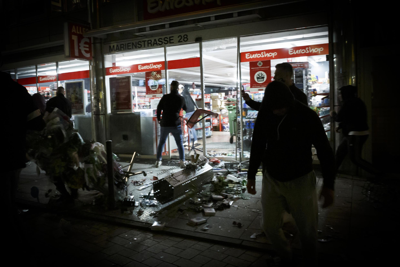 Des personnes se tiennent devant un magasin qui a été pillé à Stuttgart, en Allemagne, dans la nuit du 20 au 21 juin 2020. La ville a été le théâtre de violents affrontements entre plusieurs centaines de jeunes et la police.