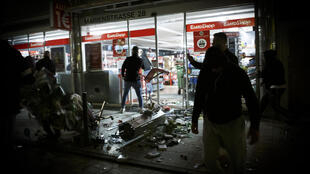People stand in front of a shop that was plundered during riots in Stuttgart, Germany on June 21, 2020.