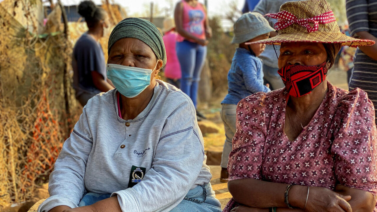 Dos mujeres esperan durante una entrega de ayudas humanitarias durante la celebración del Día de Mandela al en Johannesburgo, Sudáfrica, el 18 de Julio de 2020.
