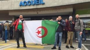 متظاهرون يرفعون علم الجزائر أمام المستشفى الذي يمكث فيه بوتفليقة بجنيف، 8 مارس/ آذار 2019.